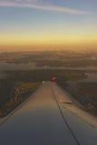从一架乘客班机的窗口的鸟瞰图在飞行中在光芒的云彩朝阳 免版税图库摄影