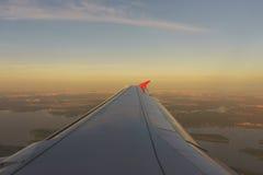 从一架乘客班机的窗口的鸟瞰图在飞行中在光芒的云彩朝阳 免版税库存图片