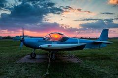 一架小体育飞机停放在机场在风景日落 免版税库存图片