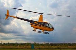 一架小黄色直升机离开 暴风云在背景中 一个小私有机场在日托米尔州,乌克兰 免版税库存图片