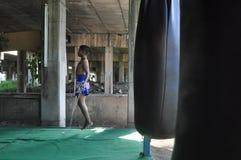 一架年轻泰国泰拳战斗机跳跃绳子在一间把装箱的健身房在一座桥梁下在Minburi,泰国 图库摄影