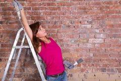 一架梯子的妇女画家在砖墙附近 库存图片