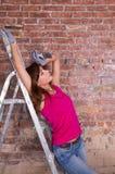 一架梯子的妇女画家在砖墙附近 免版税库存图片