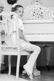 一架白色大平台钢琴的小女孩 免版税库存图片