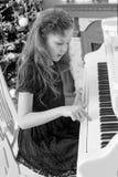 一架白色大平台钢琴的小女孩 图库摄影