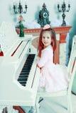 一架白色大平台钢琴的小女孩 免版税库存照片