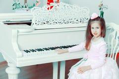 一架白色大平台钢琴的小女孩 库存图片