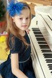 一架白色大平台钢琴的小女孩 库存照片