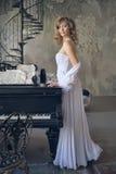 一架白色礼服和钢琴的女孩 免版税图库摄影