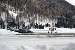 一架直升机和一个私人喷气式飞机在阿尔卑斯瑞士的多雪的风景和山 免版税库存照片