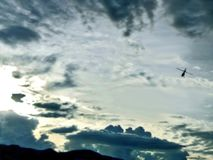 一架直升机的剪影反对灰色天空的与云彩 免版税库存照片