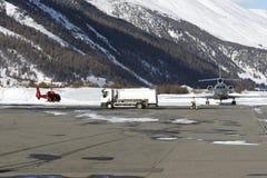 一架红色直升机、一辆加油车和一个私人喷气式飞机在圣盛生机场在多雪的阿尔卑斯瑞士在冬天 库存照片