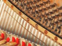一架落寞老被风化的钢琴的串和机械工 免版税库存图片
