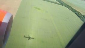 一架飞行飞机的阴影在地面上的在一个晴天 在飞机飞行地产海景视窗之上 飞机的阴影 飞过 影视素材