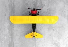 一架黄色和黑双翼飞机的上部视图在地面的 库存图片