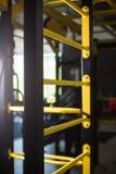 一架黄色瑞典梯子的特写镜头在被弄脏的背景的 金属瑞典人梯子 健身房内部 激活炫耀生活方式 免版税库存照片
