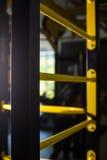 一架黄色瑞典梯子的特写镜头在被弄脏的背景的 金属瑞典人梯子 健身房内部 激活炫耀生活方式 库存图片