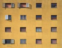 一栋居民住房的黑暗的黄色门面与棕色快门的 免版税库存图片