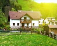 一栋白色乡间别墅的经典门面有一个绿色草甸和森林的在背景中,在一个小水池的庭院里 免版税库存图片