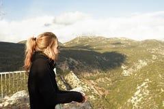 一根中年妇女,被染的头发,毛线衣和围巾,在山的观点站立 免版税库存图片