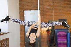 一根杆的女孩在做锻炼的健身房 免版税库存照片