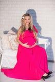 一根美丽的孕妇明亮的礼服和长的头发的画象 免版税库存图片