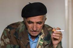 一根老人抽烟的香烟的画象 免版税库存照片