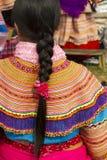 一根花Hmong礼服和头发在Bac Ha早晨市场上 免版税库存图片