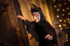 一根衣服棒的男孩在黑暗的背景,神奇童年H 库存照片