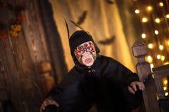 一根衣服棒的男孩在黑暗的背景,神奇童年H 库存图片