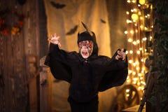 一根衣服棒的男孩在黑暗的背景,神奇童年H 免版税库存照片