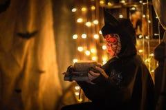 一根衣服棒的男孩在黑暗的背景,神奇童年H 免版税图库摄影