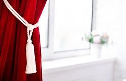 一根装饰鞋带收集的深紫红色帷幕在窗口附近 免版税库存图片