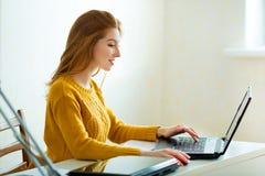 一根黄色毛线衣和红色头发的美丽的女孩 免版税库存图片
