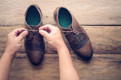 一根年轻人鞋带的手在木地板上的 库存照片