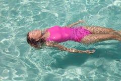 一桃红色泳装放松的美女 免版税库存照片