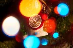 一棵圣诞树的一件装饰品以时钟的形式和诗歌选的强光 新年度 免版税库存图片