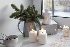 一棵圣诞树的分支在锌投手的在窗口 诗歌选被点燃,并且蜡烛烧 免版税库存图片