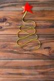 以一棵圣诞树的形式丝带在木背景 免版税库存照片