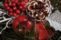 一棵圣诞树的红色莓果、苹果和分支在雪下的 圣诞节丝带 库存照片