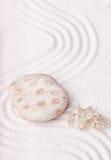一棵多斑点的岩石和干海草在禅宗庭院的美好的沙子 免版税库存照片