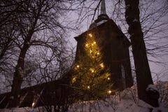 一棵明亮的圣诞树和一个老教会 免版税库存图片