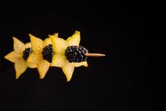 一棵明亮的黄色健康的阳桃的特写镜头在一根棍子的用在深黑色背景的一个黑水多的黑莓 免版税库存图片