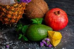 一棵有机鲕梨、水多的石榴石、椰子和黄色阳桃的一张顶视图在深灰背景 库存图片