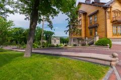 一棵树在生长在绿色草坪的公园在导致一个别致的房子的一个被铺的走道旁边 库存照片
