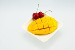 一棵白色板材、芒果和樱桃樱桃,匙子 免版税库存图片