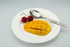 一棵白色板材、芒果和樱桃樱桃,匙子 库存图片