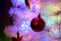 一棵白色xmas树的特写镜头与一个深红装饰球的 库存照片