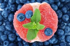 一棵苦涩葡萄柚、甜蓝莓和新鲜薄荷作为背景 滋补柑橘在越桔的中心 免版税库存图片