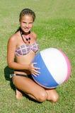 一棵草的女孩与一个可膨胀的球 免版税库存照片